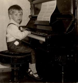 Alte schwarz weiß Aufnahme von Daniel Herzig als Kind an einem Klavier